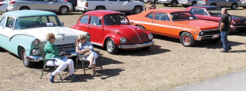 Two women sitting in chairs converse in front of classic cars
