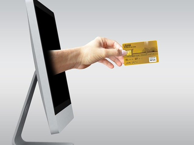 A hand holding a credit card reaches out of computer screen