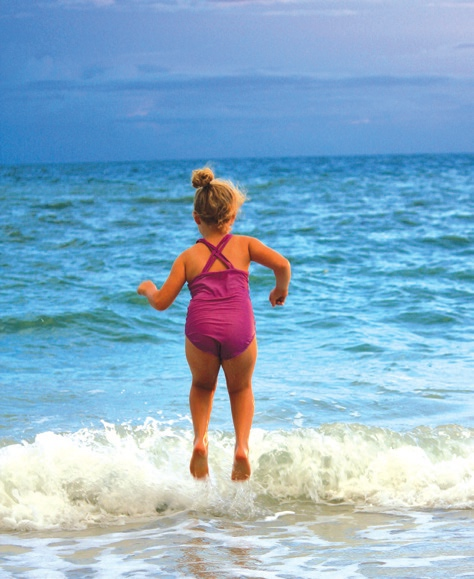 A girl in a bathing suit leaps into the air as the tide comes in