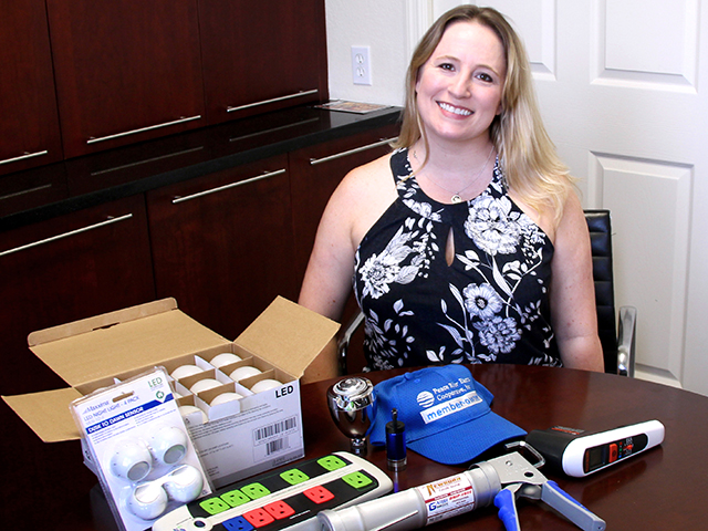 Kathy Exon at a table with energy efficiency kit items
