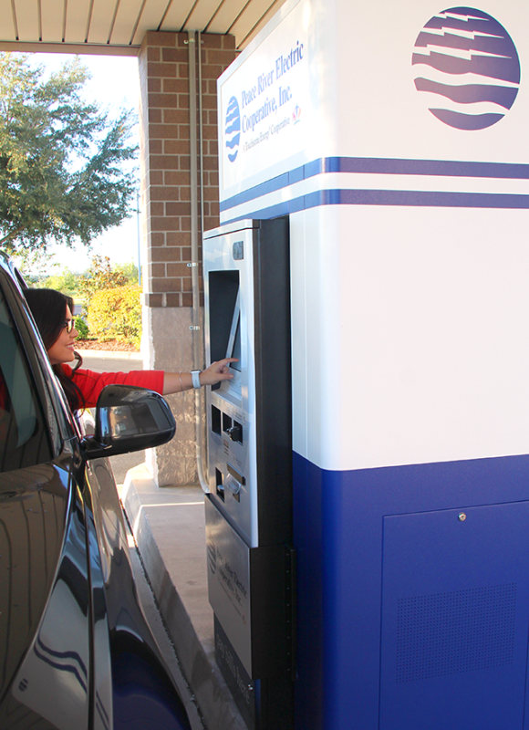 Female in car uses PRECO payment kiosk
