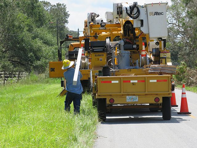 A lineman works on the side of the roadway