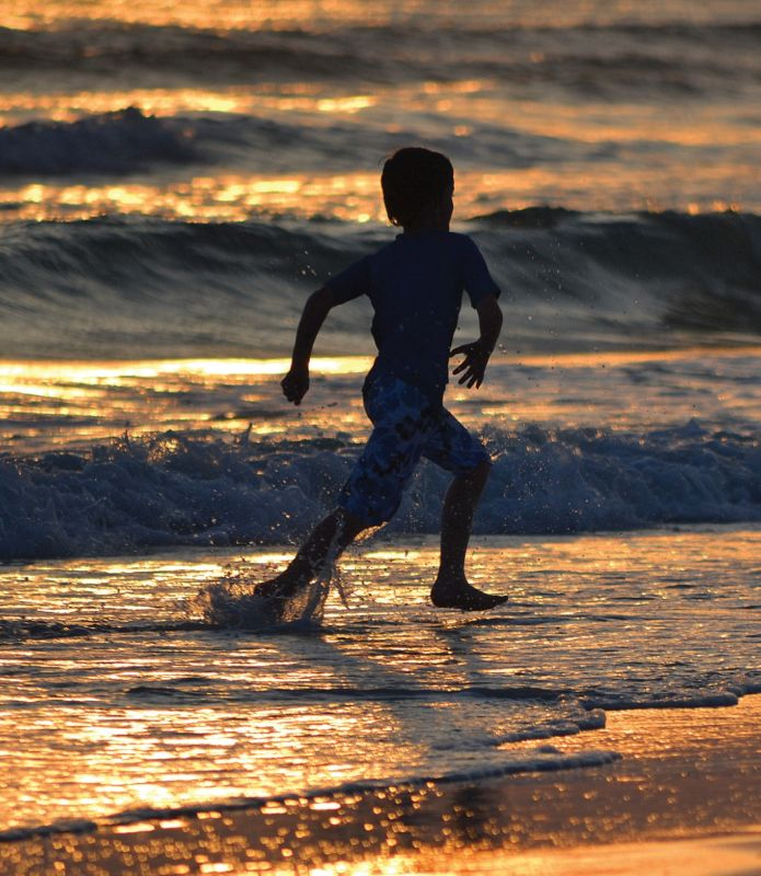 Photo of a boy running across the tide as the sun sets