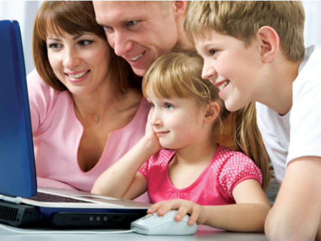 Family gathers around a laptop computer