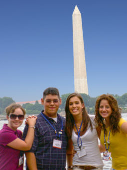 4 people stand with the Washington Monument in the background