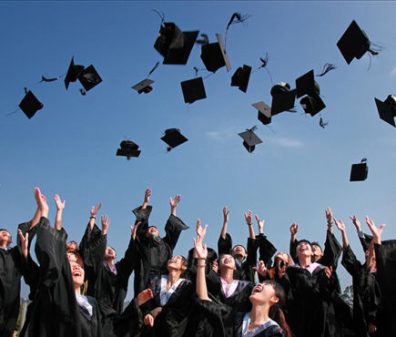 Graduates throw caps into the air